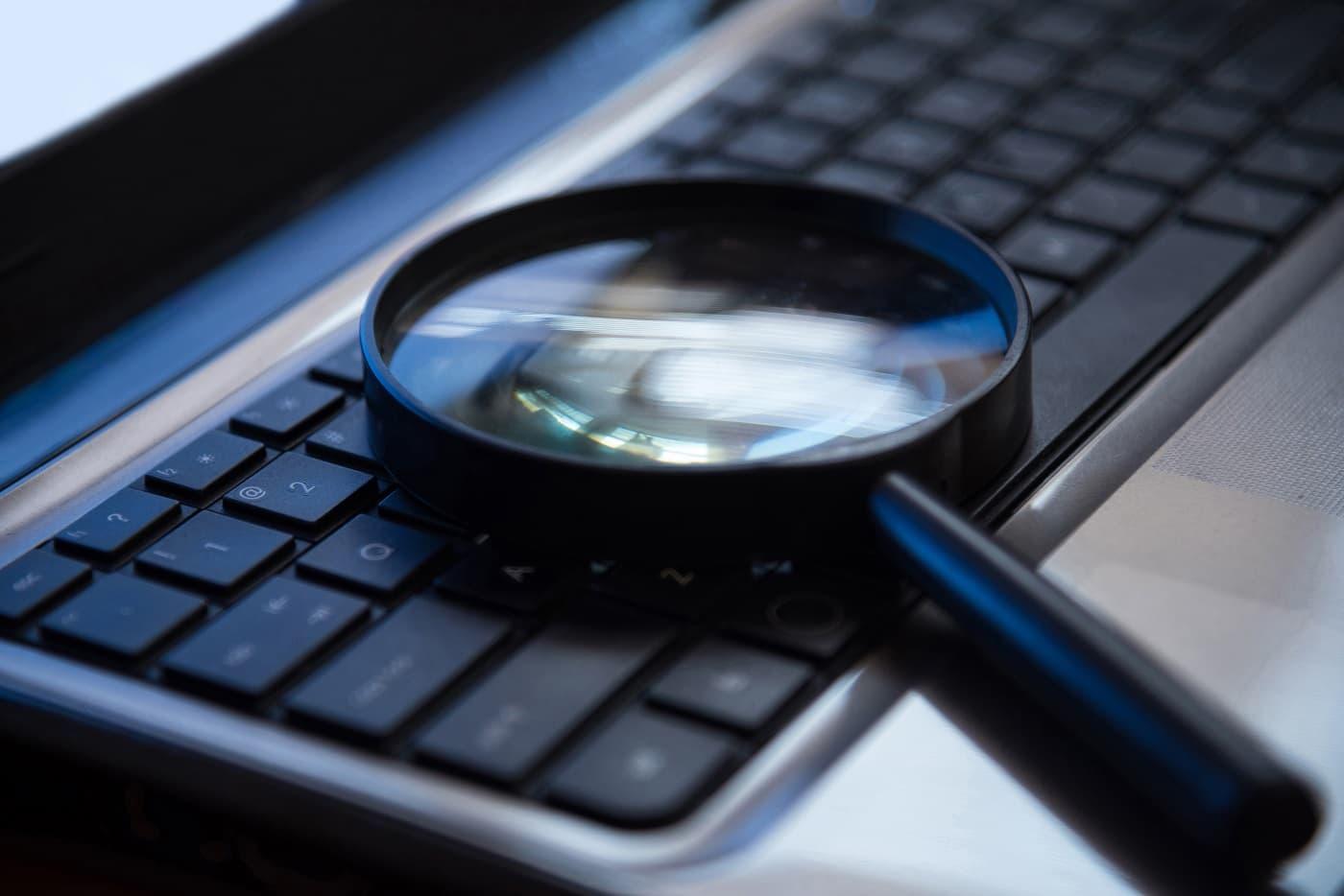 Lupa sobre ordenador protección datos detectives privados